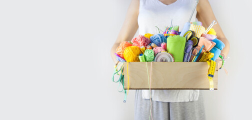 woman holds basket with accessories for needlework