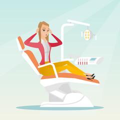 Afraid woman sitting in the dental chair.
