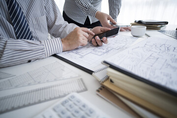 Men and women have smartphones on the design drawing