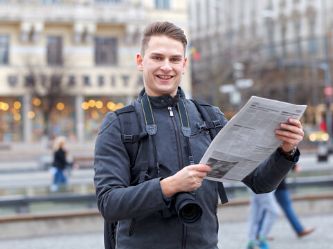 Young traveler at a public square reading newspaper