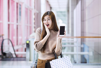 Asian girls with shopping bags using smartphone