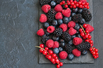Mix of berries raspberries red currants and blueberries on black slate board. Gray stone background.  Top view.