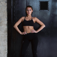 Confident Caucasian fitness model in black sportswear standing hands on hips looking at camera posing against black door