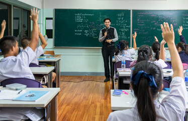Asian teacher Giving Lesson over the the physics formular in thai laguage on black board in school classroom and students showing the hand for answer,school education concept,The teacher wrote himself