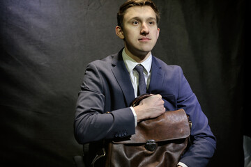 Young man in dark blue business suit sits with suitcase