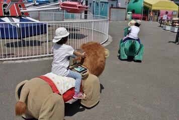 遊園地の動物の乗り物に乗る子供たち