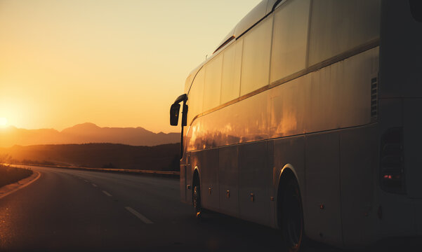 bus driving on road towards the setting sun