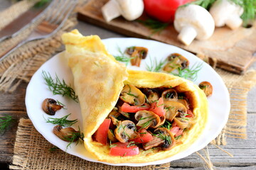 Vegetarian omelette recipe. Mushrooms omelette with tomatoes and dill on a plate. Fork, knife, fresh mushrooms, tomatoes, dill on a vintage wooden background. Easy breakfast omelette. Rustic style