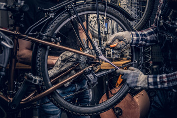 Mechanic fixing rear derailleur from a bicycle.