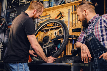 Two bearded mechanics fixing bicycle's wheel in a workshop.