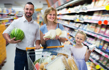 Adult parents with girl shopping in hypermarket