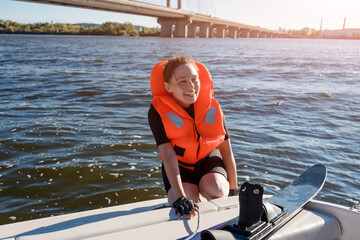 Young fit woman ready to ride water skis siting on the boat closeup. Athlete water skiing and having fun. Living a healthy lifestyle and staying active. Water sports theme