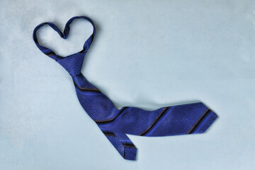 Happy Fathers Day! Classic blue tie on a blue background, heart shape. Conception of congratulation on Father's Day.