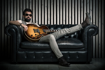 adult caucasian guitarist portrait with electric guitar sitting on vintage sofa. Music singer concept on couch and modern wood wall