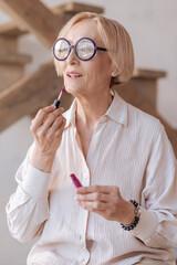 Old woman testing new lip-gloss