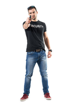 Undercover police man holding gun in one hand pointing at you.  Full body length  portrait isolated on white studio background.