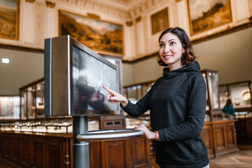 A woman in the museum uses the touchscreen monitor electronic guide, the concept of modern education Fototapete