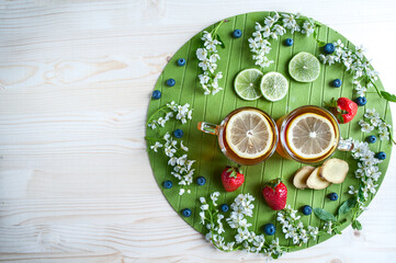 Tea background, top view, space for text.  Black tea with lemon, ginger, lime, mint,  Light green, mint background. Decorated with white cherry flowers.