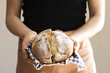 Female hand holding hot freshly baked bread