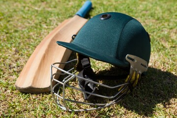 High angle view of cricket helmet and bat on field