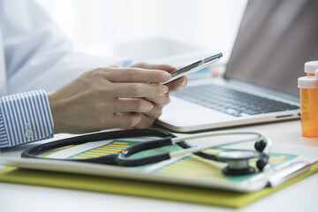 Female doctor is watching smartphone in medical office