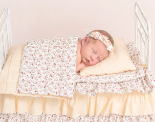Infant in hairband napping under the sheets