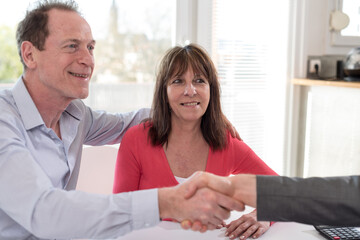 Senior couple shaking hands with realtor
