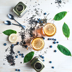 Tea background, top view. Black tea with lemon, ginger, lime, mint, lemon ,. Light wooden background.Food industry, tea packing, restaurant business
