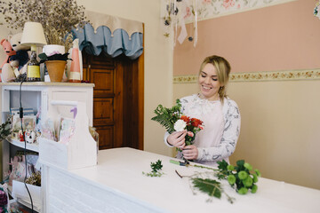 woman florist making bouquet of flowers indoor. Female florist preparing bouquet with roses and carnations in flower shop