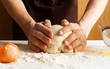 Man cooks in the kitchen preparing dough
