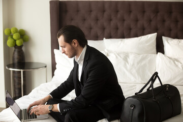 Serious man wearing business suit working on laptop while sitting on bed with luggage in luxury apartment. Businessman finishing presentation in hotel room before going on meeting with foreign partner