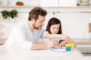 Father and his daughter engaged in the painting process