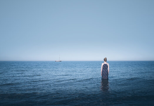 rear view of young blonde caucasian woman wearing a blue dress standing in shallow ocean water with sailboat at horizon under clear blue sky