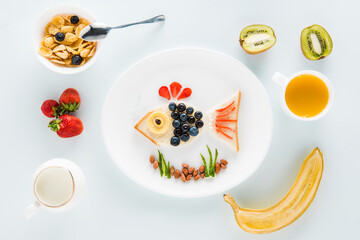 Top view of funny homemade sandwich in shape of fish and fruits with cereal flakes