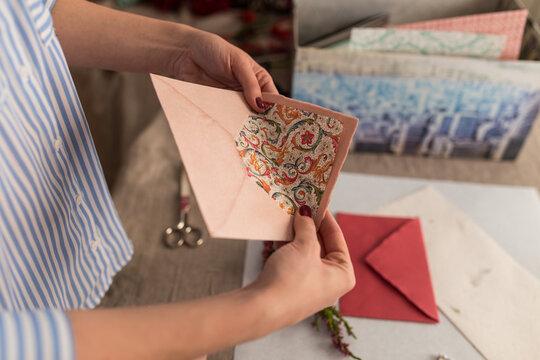 Crop woman in workshop decorating envelopes