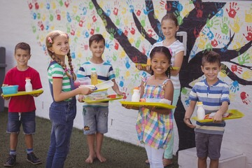 Portrait of happy schoolkids holding meal in tray