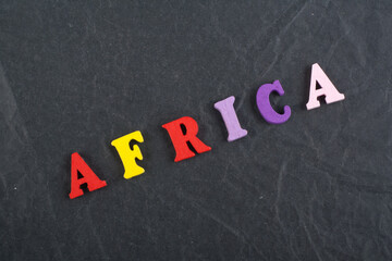 Africa word on black board background composed from colorful abc alphabet block wooden letters, copy space for ad text. Learning english concept.