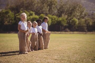 Portrait of happy schoolgirls standing in sack during race