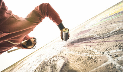 Lower view of street artist painting graffiti on generic wall - Modern art concept with urban guy performing and preparing live murales with green aerosol color spray - Warm retro backlight filter
