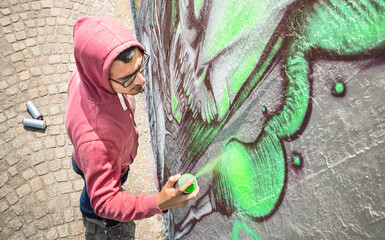 Street artist painting colorful graffiti on generic wall - Modern art concept with urban guy performing and preparing live murales with green aerosol color spray - Sunny afternoon neutral filter