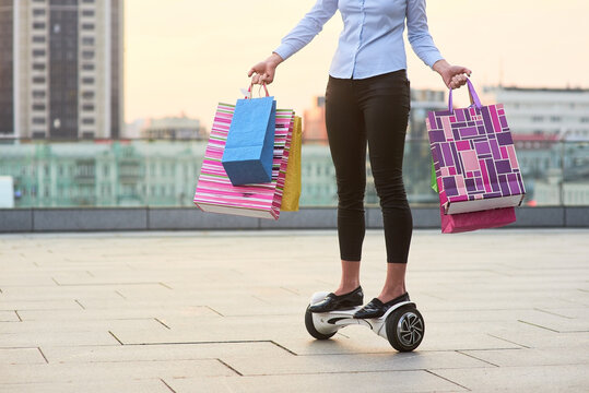 Woman holding colorful bags. Person riding gyroscooter. Ultimate shopping guide.