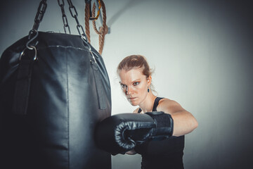A young woman leans hands of black punching bag