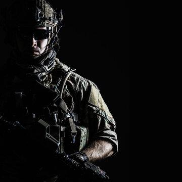 Elite member of US Army rangers in combat helmet and dark glasses. Studio shot, dark black background, looking at camera, dark contrast