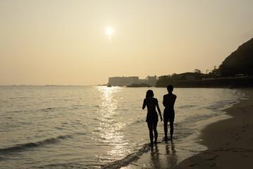 夕日のビーチで寄り添うカップル