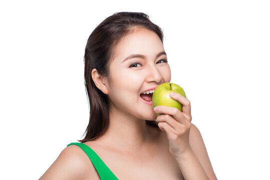 Young beautiful asian woman eating fresh green apple on white background