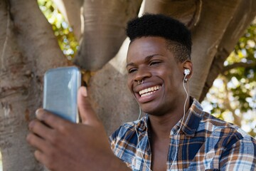 Young man with earphones listening to music on mobile phone