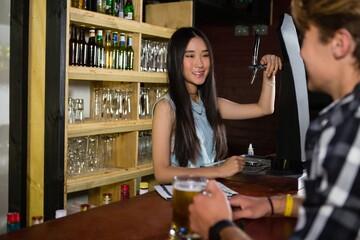Female bartender preparing drink at counter