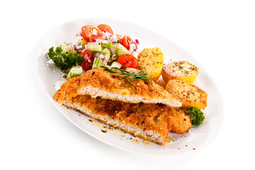 Fried pork chop with tomatoes and vegetable salad on white background