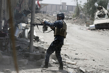 A member of the Iraqi Federal Police fires against Islamic State positions at the frontline in western Mosul