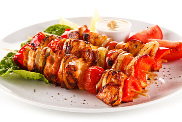 Roast meat with vegetables on stick on white background